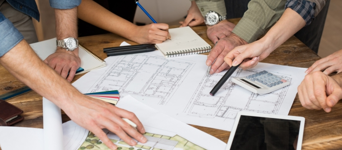A group of people working on blueprints and floorplans