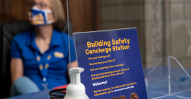Provost Anne Cudd seated at a Building Safety Concierge station inside the Cathedral of Learning.
