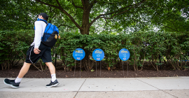A masked person walking past Power of Pitt signs on campus.